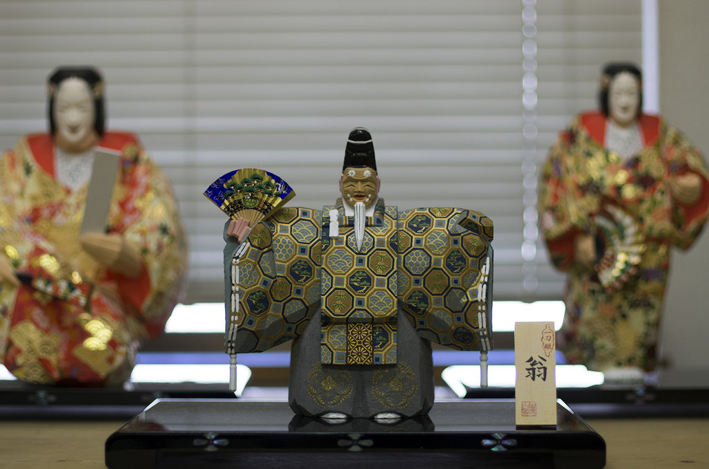 Figurine représentant Okina, personnage divin qui souhaite la paix et la stabilité du pays. Dans le théâtre nô, il est joué par l'acteur principal qui porte un masque de vieillard souriant.