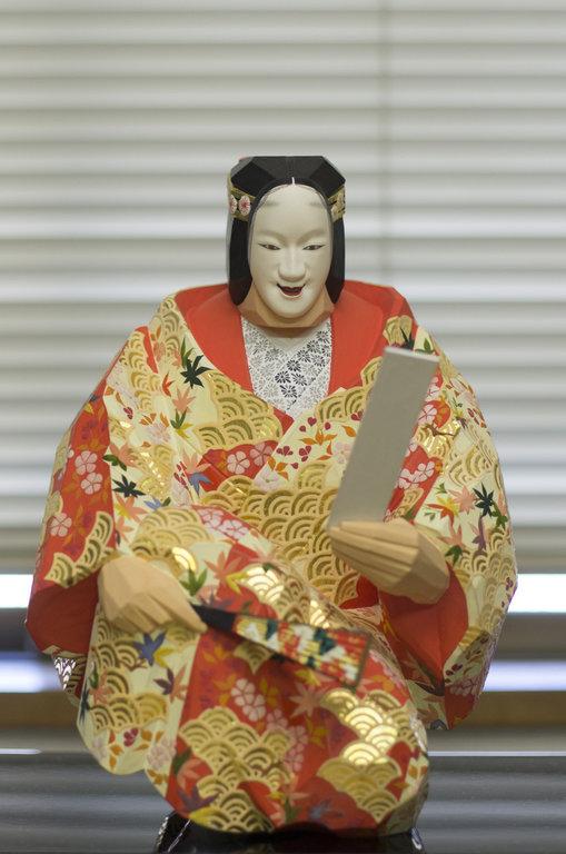 Statuette d'une trentaine de centimètres de haut représentant Yuya, personnage de la pièce de nô du même nom. Amoureuse d'un samouraï, elle est ici en train de lire un waka, poème de trente et une syllabes.