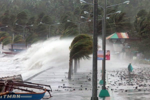 Un résident passe devant les énormes vagues provoquées par le typhon Haiyan alors qu'il touche la ville de Legaspi, dans la province d'Albay au sud de Manille, le 8 novembre 2013.
