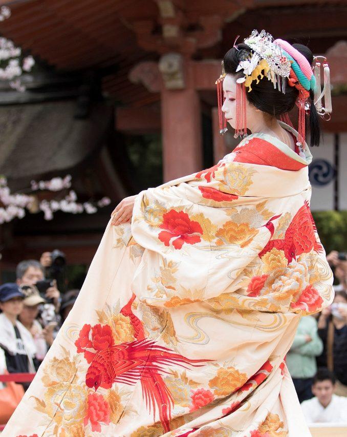 Représentation d'Aoitayû au sanctuaire Iwashimizu Hachimangû, dans le département de Kyôto, en avril 2016. Les tayû se distinguent entre autres des geishas par l'extravagance de leur chevelure et leur rouge à lèvre, qui ne recouvre que la lèvre inférieure.