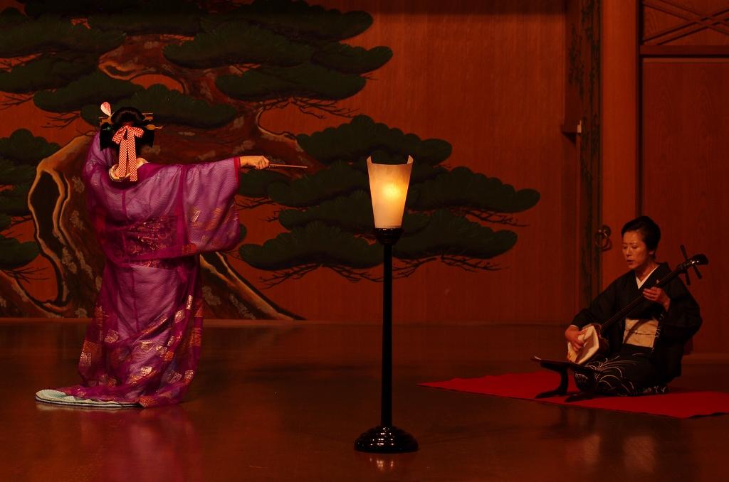 Danse de Tsukasadayû sur une scène de nô, accompagnée d'une joueuse de shamisen, instrument de musique traditionnel à trois cordes. L'actrice a choisi une tenue discrète, comme c'était le cas il y a environ 250 ans, contrairement à l'extravagance générale qui caractérise l'habillement et la chevelure des tayû.