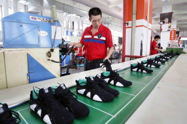 Un ouvrier chinois examine des chaussures de sport dans une manufacture de Jinjiang, dans la province du Fujian au sud-est de la Chine, le 27 juillet 2016.