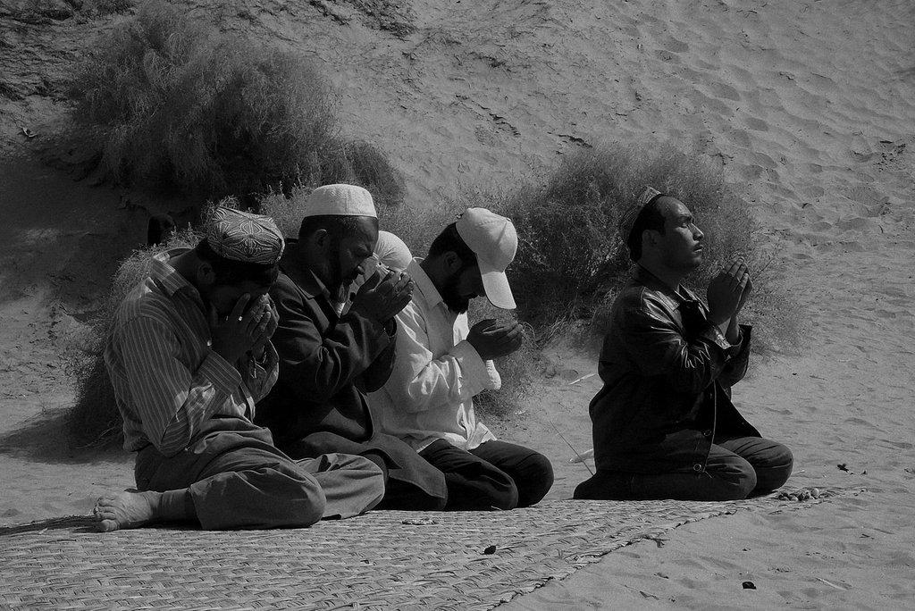 Des hommes prient devant la tombe d'un saint, désert du Takla-Makan, région de Hotan. (Crédit : Ma Kang).