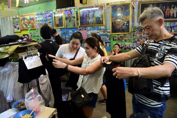 Des Thaïlandais achètent des vêtements noirs pour le deuil dans un magasin de Bangkok, aux murs couverts de portraits du défunt roi Bhumibol Adulyadej, le 15 Octobre 2016.