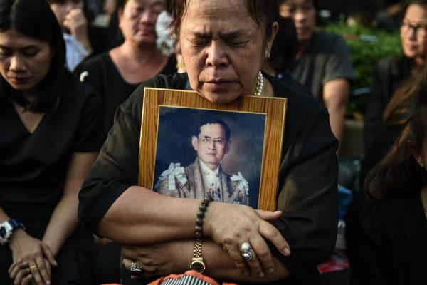 Une Thaïlandaise se recueille après le passage du corbillard transportant le corps du roi Bhumibol Adulyadej devant le Grand Palais à Bangkok, le 14 octobre 2016.