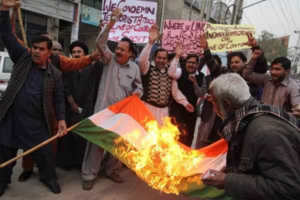 Des manifestants pakistanais brûlent un drapeau indien à Multan le 23 novembre 2016, suite aux tirs indiens transfrontaliers ayant fait 12 victimes dont 9 civils. (Crédit : SS MIRZA / AFP)