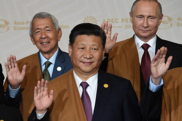"""Le président chinois Xi Jinping entouré de son homolgue russe Vladimir Poutine et du ministère philippin des affaires étrangères Perfecto Yasay, lors de la tradutionnelle """"photo de famille"""" de l'APEC (Asia-Pacific Economic Cooperation) au Centre des Conventions de Lima au Pérou le 20 novembre 2016."""