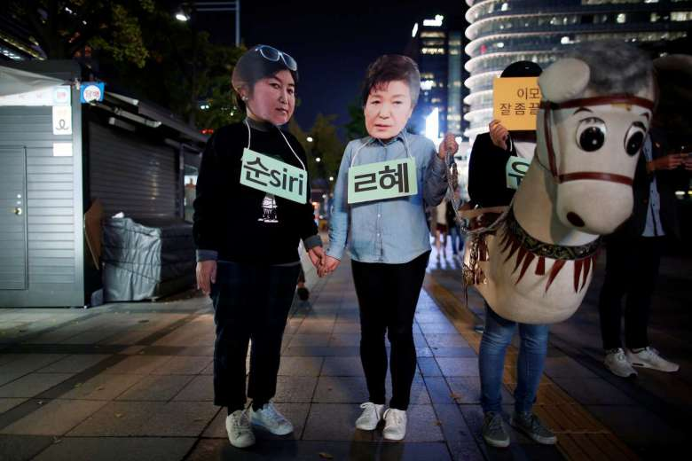 Des manifestants sud-coréens portant le masque de la présidente Park Geun-hye et de sa confidente Choi Soon-sil lors d'un rassemblement contre Park, à Séoul le 27 octobre 2016 (Crédits : REUTERS). Copie d'écran du Korea Times, le 3 novembre 2016.
