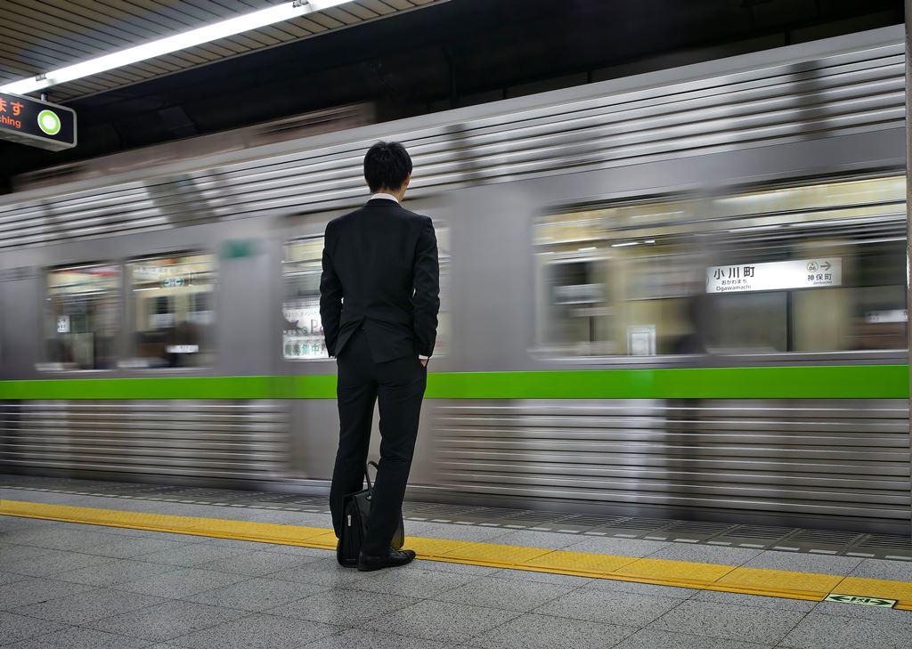 """Un """"salaryman"""" sur le quai d'une gare de Tokyo."""