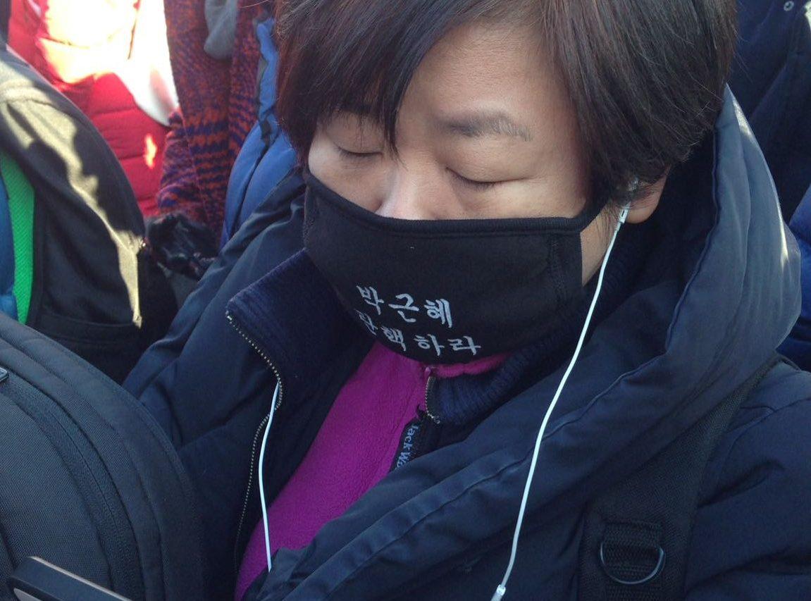 """En Corée du Sud, une femme, parmi la foule des manifestants en colère sur la place de Yoeido à Séoul le vendredi 9 décembre, prend connaissance sur son portable des résultats du vote par le Parlement. Sur son masque, en lettres blanches : """"Park Geun-hye, destitution !"""" (Copyright : Dorian Malovic)"""