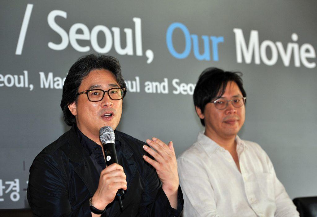 """Le réalisateur sud-coréen Park Chan-wook (au micro) lors le 20 août 2013 lors d'une conférence de presse pour la promotion du projet """"Seoul: Our Movie"""" à Seoul. (Crédits : AFP PHOTO / JUNG YEON-JE / AFP PHOTO / JUNG YEON-JE)"""