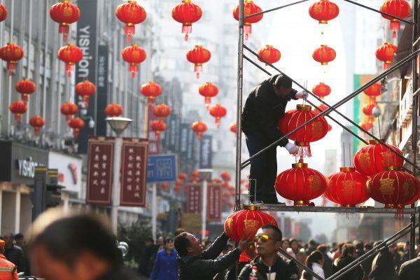 Des ouvriers chinois installent des lanternes dans la ville de Wenzhou (province du Zhenjiang) à l'approche du nouvel an, le 23 janvier 2017. (Crédit : CHANG KONG / IMAGINECHINA via AFP)