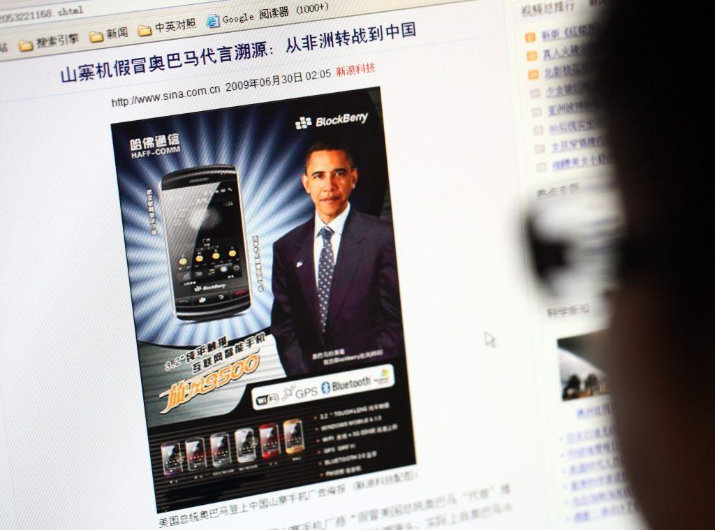 """Un Internaute face à la publicité d'une marque chinoise de smartphone """"shanzhai"""" nommée """"Blockberry"""", utilisant l'image de Barack Obama. à Shanghai, le 20 septembre 2010. (Crédits : Zhou junxiang / Imaginechina / via AFP)"""