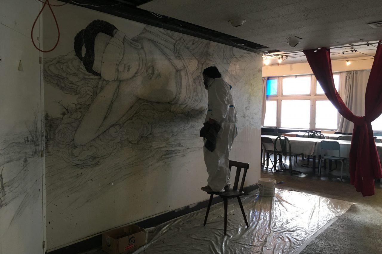 """L'artiste chinois Fansack en train de réaliser la fresque """"Parinirvana no.5"""" à l'exposition """"Troposphère"""" au 6B à Saint-Denis. (Crédit : DR)"""