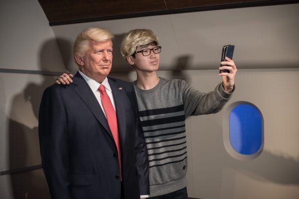 Un visiteur se prend en photo devant le mannequin de cire de Donald Trump au musée Grévin de Séoul, le 20 janvier 2017. (Crédits : Ed JONES / AFP)