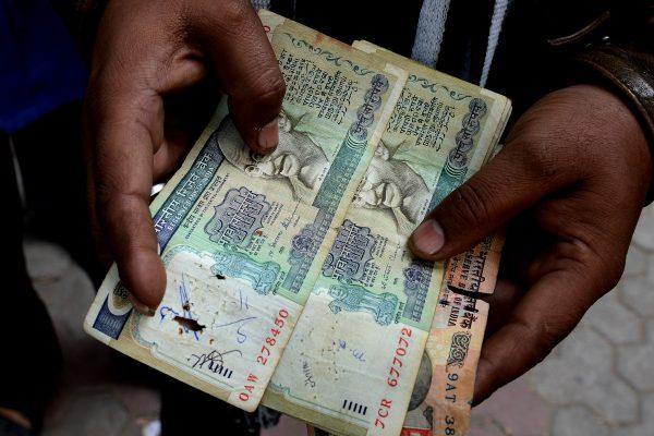 Un Indien posté devant la banque centrale à New Delhi le 30 décembre 2016, montre de vieux billets de banque frappés d'invalidité par l'opération de démonétisaiton lancée par le Premier ministre Narendra Modi le 8 novembre 2016. (Crédits : Money SHARMA / AFP)