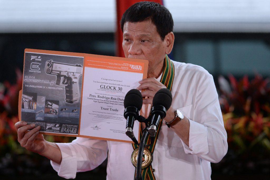 """Le président philippin Rodrigo Duterte tient un certificat de détention d'un pistolet Glock 30, remis à lui par un importateur d'armes à feu en récompense de sa lutte anti-drogue, lors d'une """"causerie aux soldats"""" à Manille, le 4 octobre 2016. (Crédits : AFP PHOTO / TED ALJIBE)"""