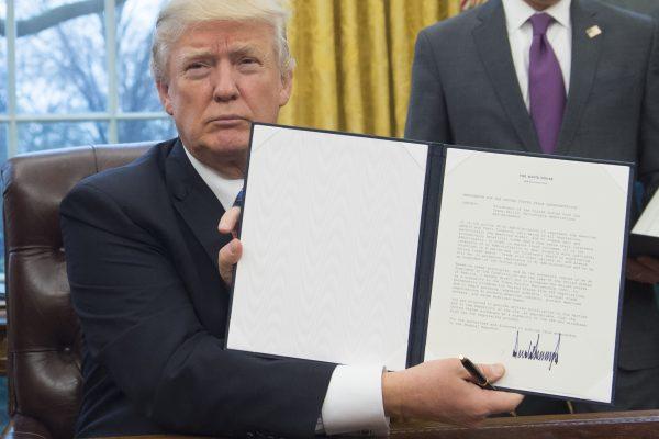 Le président américain Donald Trump présente le décret qu'il vient de signer pour retirer les Etats-Unis du Partenariat transpacifique, dans le bureau oval de la Maison-Blanche à Washington, le 23 janvier 2017. (Crédits : AFP PHOTO / SAUL LOEB)