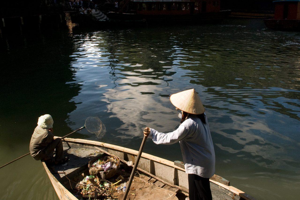 Collecte des déchets rejetés par les bateaux de tourisme dans la baie d'Halong, le 24 juillet 2015. (Crédits : Sergi Reboredo / picture alliance / DPA / via AFP)