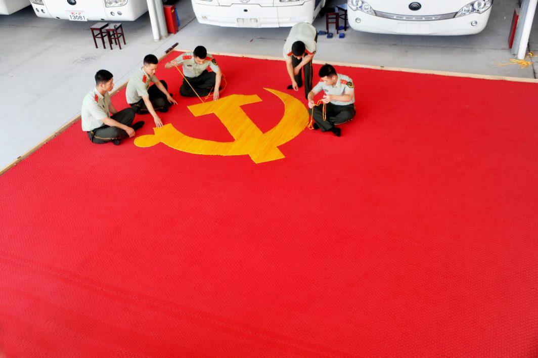 A la veille des célébrations des 95 ans du Parti Communiste Chinois le 30 juin 2016, des membres du Parti cousent un drapeau.