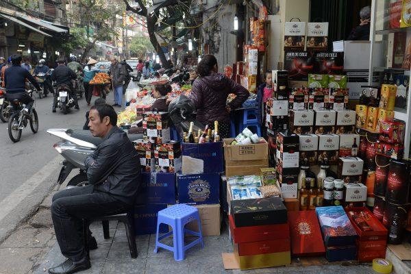 Un homme assis devant une boutique du centre-ville de Hanoi proposant du vin, des chocolats et autres boissons au moment des célébrations du Tet, le 23 janvier 2017.