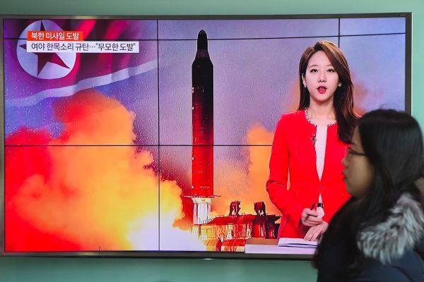 """Une passante devant un écran de télévision montrant les images du tir """"réussi"""" d'un missile à portée intermédiaire par la Corée du Nord, à Séoul le 12 février 2017. (Crédits : JUNG Yeon-Je / AFP)"""