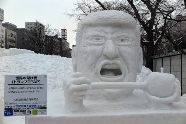 Un buste géant du président Donald Trump tout en neige, s'apprêtant à mordre dans un stylo planté dans un ananas, au festival de la neige à Sapporo, le 6 février 2017. (Crédits : Lars Nicolaysen/dpa/via AFP)