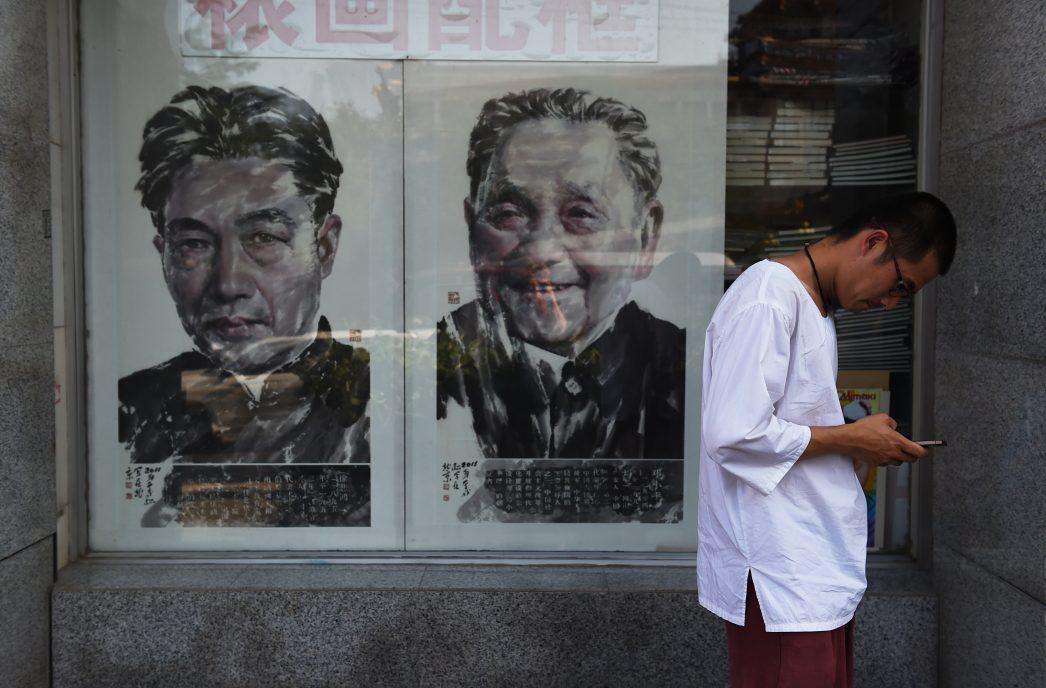 Un homme consulte son téléphone portable devant une affiche présentant les portrait de Deng Xiaoping (à droite) et de Xu Beihong (à gauche) à Pékin, le 10 août 2015.
