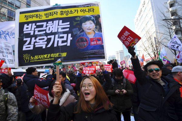 """Des militants anti-gouvernement célèbrent la destitution de la présidente sud-coréenne Park Geun-hye en brandissant des panneaux """"Park Geun-Hye en prison !"""" à Séoul le 10 mars 2017. (Crédits : AFP PHOTO / JUNG Yeon-Je)"""