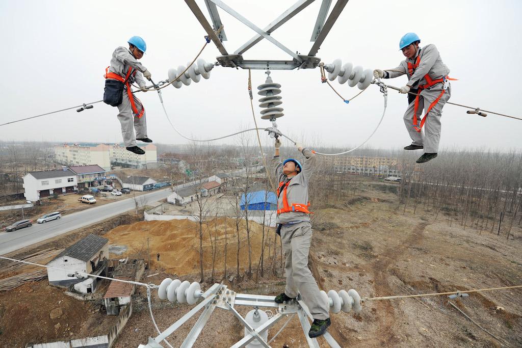 Des électriciens chinois installent des lignes à haute tension sur un pylône au-dessus du ville de Xiyang, dans la province chinoise de l'Anhui à l'est du pays, le 18 janvier 2015.