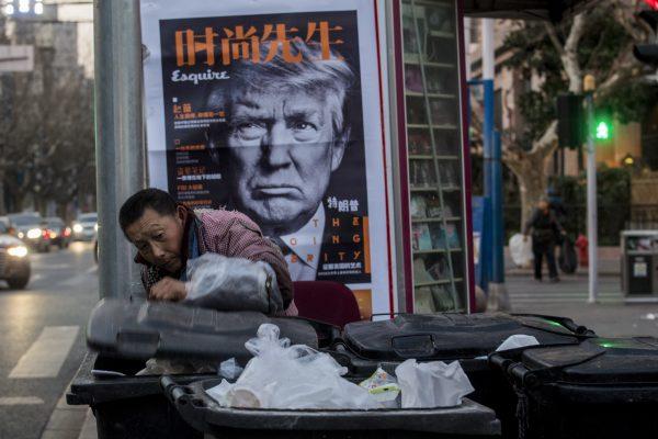 Un Chinois fouille des bennes à ordures devant un kiosque affichant la photo de Donald Trump en couverture du magazine chinois Esquire, le 2 mars 2017, à Shanghai. (Crédits : AFP PHOTO / Johannes EISELE / via AFP)