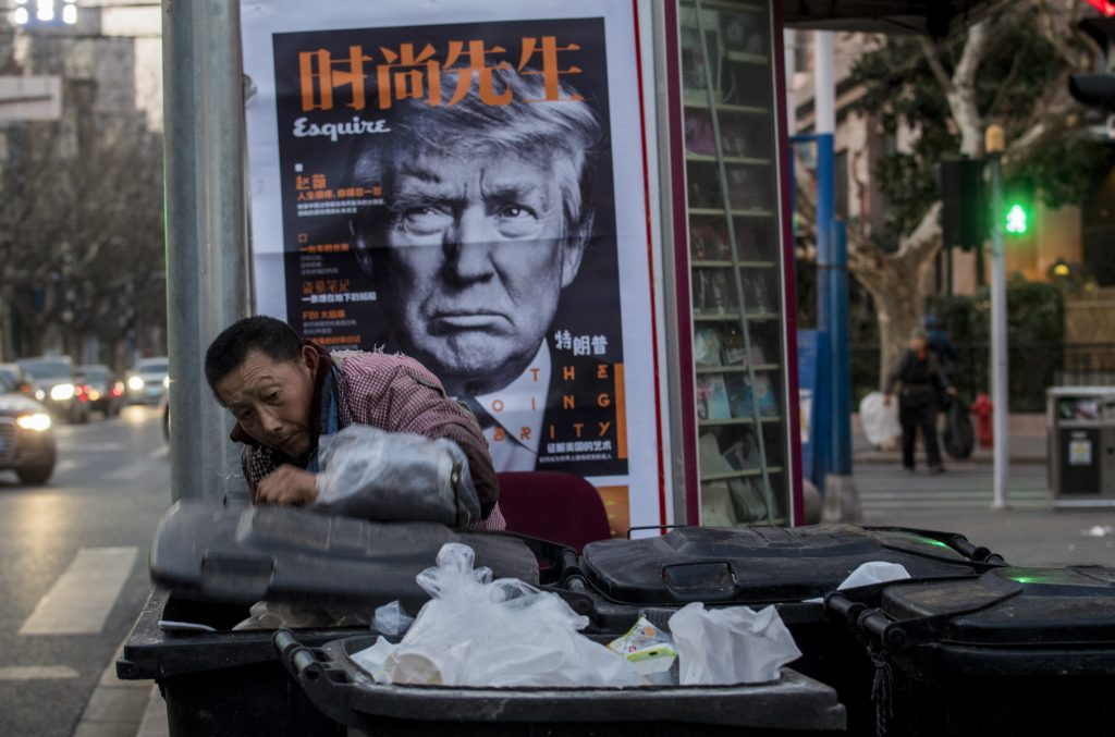 Un Chinois fouille des bennes à ordures devant un kiosque affichant la photo de Donald Trump en couverture du magazine chinois Esquire, le 2 mars 2017, à Shanghai. (Crédits : AFP PHOTO / Johannes EISELE / via AFP)