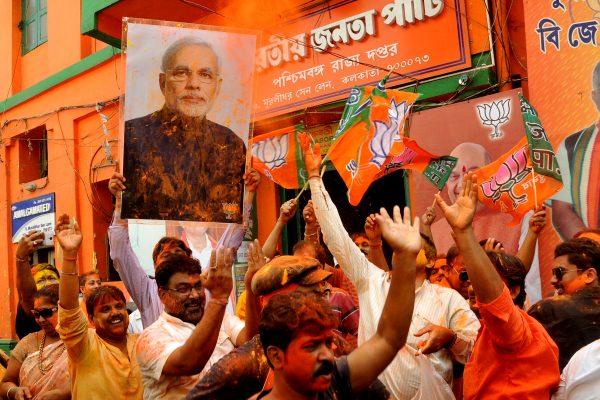 Les supporters du BJP, le parti nationaliste hindou au pouvoir, célèbrent le festival Holi en brandissant le portrait du Premier ministre Narendra Modi après l'annonce de l'écrasante victoire de son parti aux élections du parlement de l'Uttar Pradesh le 11mars 2017 à Calcutta. (Crédits : Debajyoti Chakraborty/NurPhoto/via AFP)