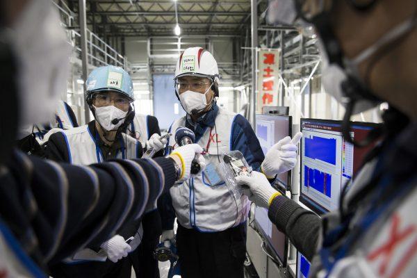 Un employé de la TEPCO (Tokyo Electric Power Co) répond aux questions des journalistes devant l'écran de contrôle d'un bâtiment réfrigéré du groupe nippon à la centrale nucléaire de Fukushima Dai-ichi à Okuma, le 23 février 2017. (Crédits : AFP PHOTO / POOL / Tomohiro Ohsumi)