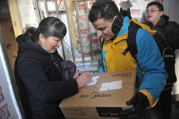 Un étudiant étranger employé par l'entreprise chinoise d'e-commerce Sunning livre un courrier à une cliente chinoise pour le Nouvel an lunaire à Nankin le 30 janvier 2016.