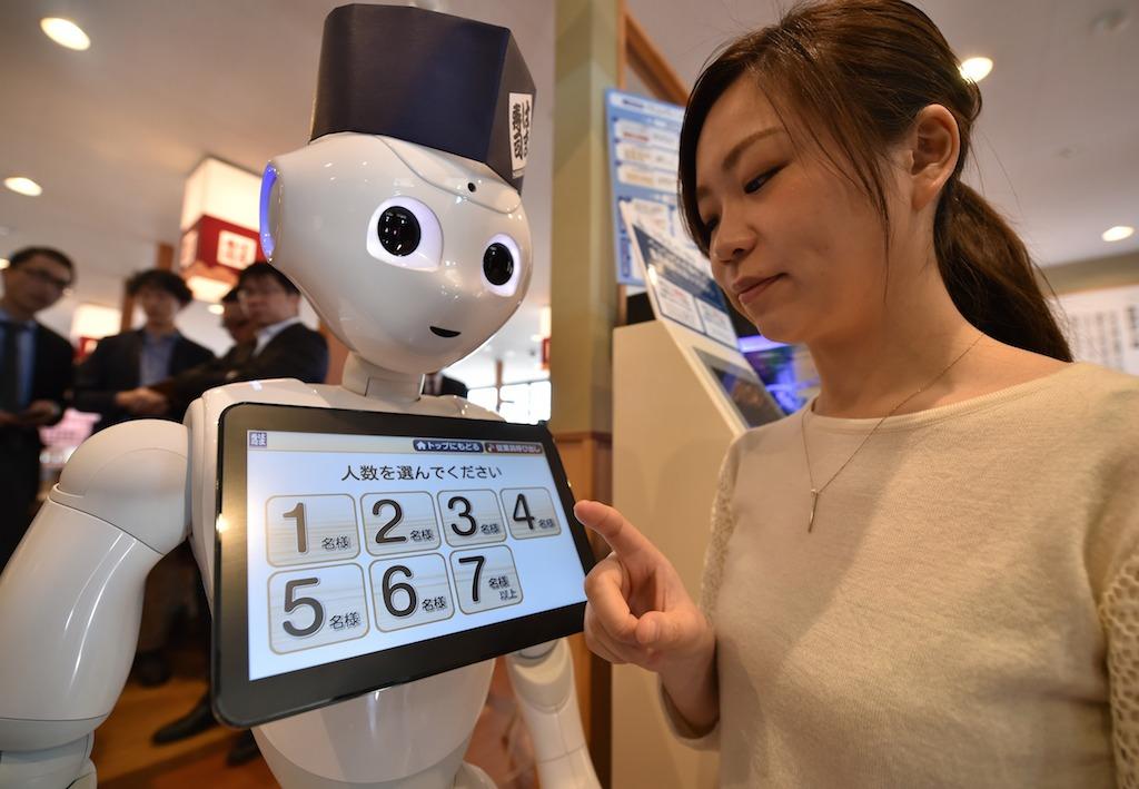 Une employée du restaurant de sushi Hamazuki près du robot Pepper créé par le géant nippon des telecom Softbank à Saitama le 2 février 2017. (Crédits : AFP PHOTO / KAZUHIRO NOGI)