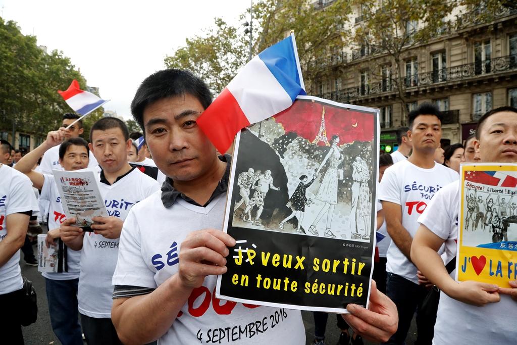 Un membre de la communauté chinoise de Paris lors de la manifestation contre l'insécurité des Asiatiques de France, organisée dans la capitale place de la République le 4 septembre 2016, après la mort de Zhang Chaoling décédé à la suite d'une agression.