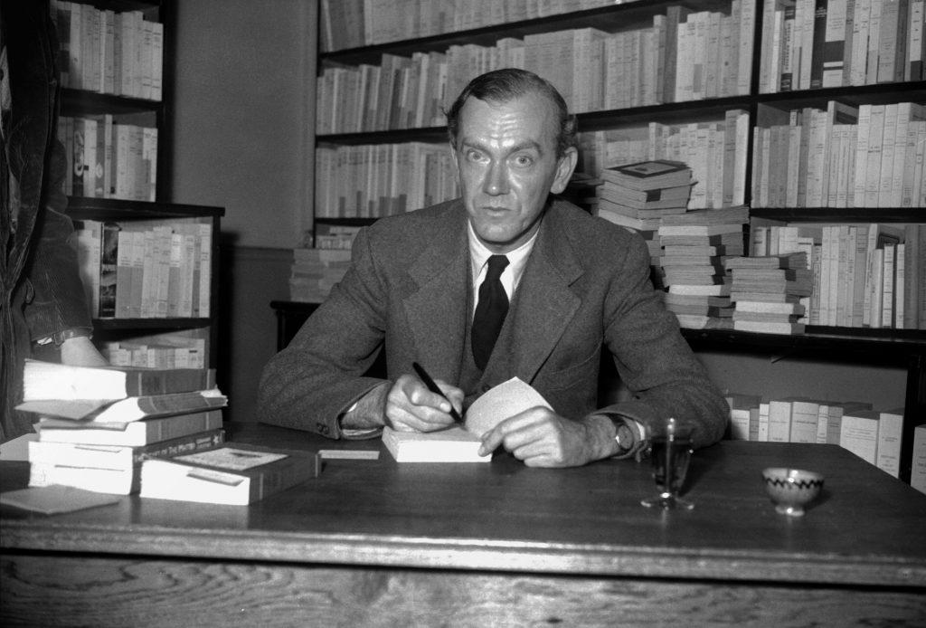 """Photo non datée de l'écrivain anglais Graham Greene dédicaçant l'un de ses romans dans une librairie. Journaliste, Graham Greene publie une série de romans comme """"L'homme et lui-même"""" (1929), """"La Puissance et la Gloire"""" (1940), """"Le Facteur humain"""", """"Le Troisième Homme"""", puis il se tourne vers l'édition et devient scénariste tant pour l'adaptation de ses romans au cinéma que pour le théâtre. (Crédits : AFP PHOTO)"""