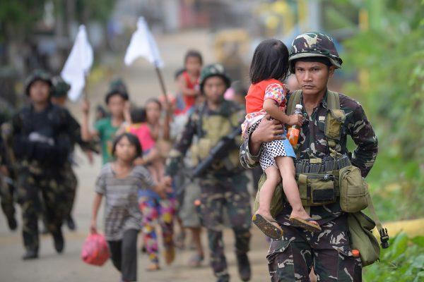 Des soldats philippins escortent les civils d'un village proche de Marawi dans l'île de Mindanao au sud des Philippines, le 31 mai 2017. (Crédits : AFP PHOTO / TED ALJIBE)