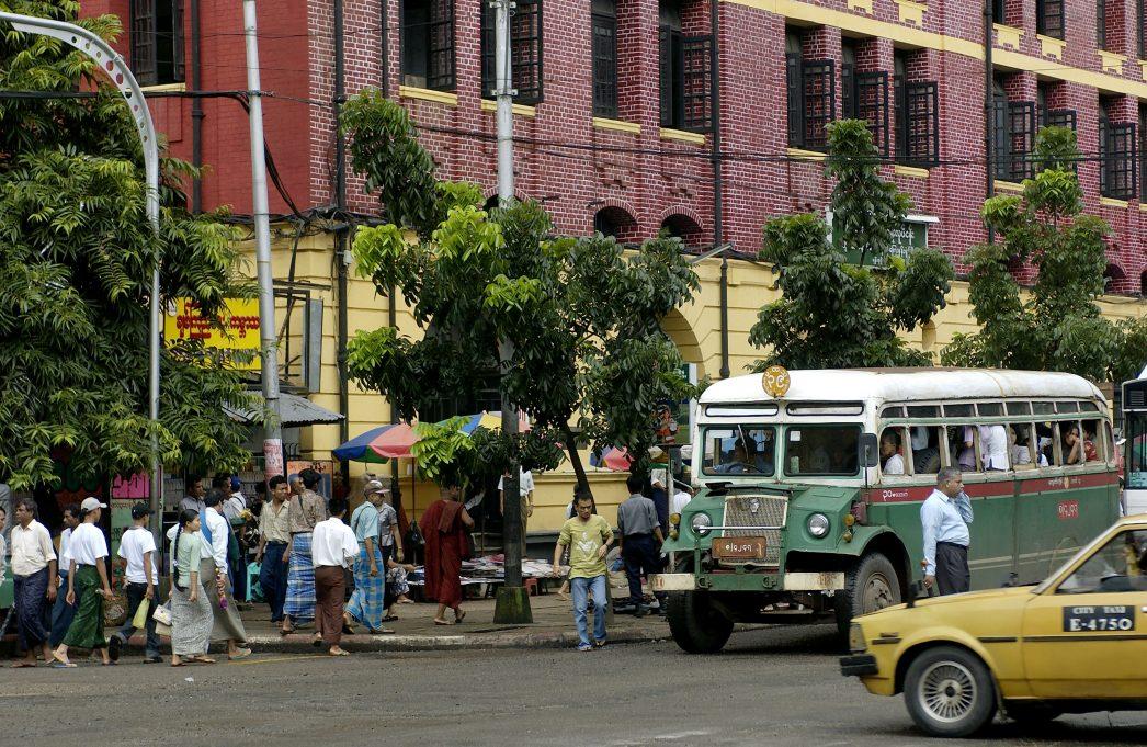 Birmanie, entre piétons et vieux bus dans la ville moderne de Rangoon.