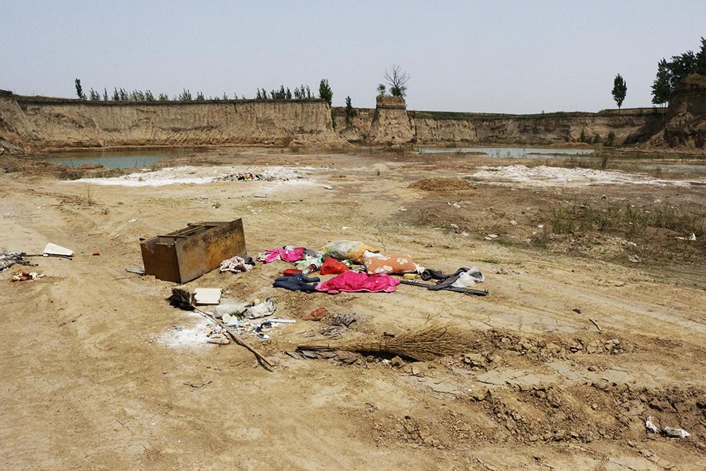 Entre deux étendues de champs de blés, une carrière artificielle, devenue décharge sauvage, témoigne de l'érosion inquiétante des sols dans la nouvelle zone économique spéciale de Xiong'an. (Copyright : Elodie Buzaud)
