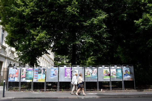 A Nantes, en France, un couple passe devant les affiches électorales des candidats de la campagne législative.