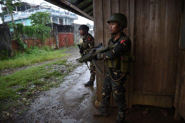 Des soldats gouvernementaux prennent position contre des snipers du groupe Maute, alors qu'ils escortent des résidents hors de Marawi au sud des Philippines, le 1er juin 2017. (Crédits : AFP PHOTO / TED ALJIBE)