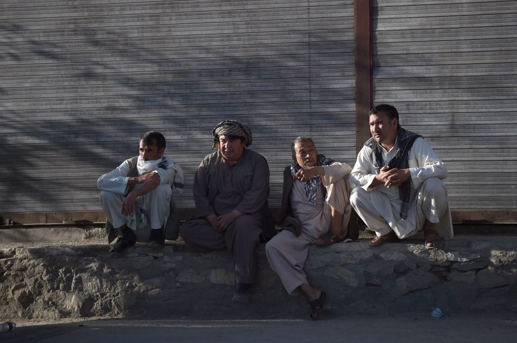 Des passants afghans près du site d' un attentat suicide à Kaboul le 16 juin 2017.