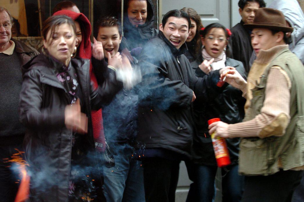 Des jeunes chinois lancent des pétards dans le quartier chinois, le 24 janvier 2004 dans le IIIe arrondissement de Lyon, à l'occasion du Nouvel-An chinois.