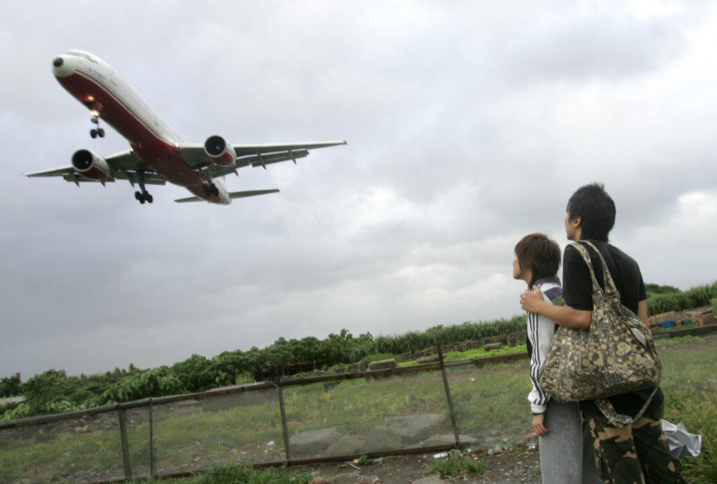 Un jeune couple regarde un avion atterrir à l'aéroport de Taipeï le 12 juillet 2006.