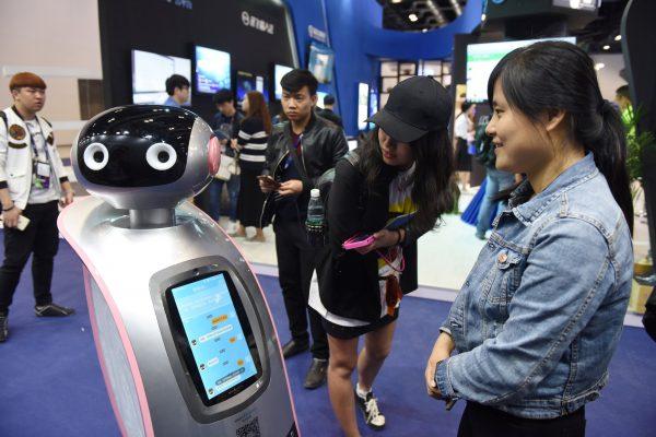 Des visiteurs chinois interagissent avec un robot lors de la Global Mobile Internet Conference (GMIC) à Pékin le 27 avril 2017. (Crédits : AFP PHOTO / Greg Baker)