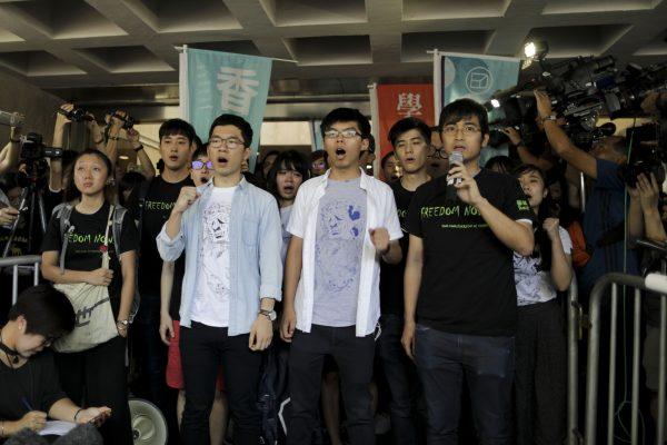 Les trois leaders du mouvement des parapluies, (de gauche à droite) Nathan Law, Joshua Wong et Alex Chow, chantent des slogans avant leur condamnation à de la prison ferme le 17 août 2017 à Hong Kong. (Crédits : EyePress News / EyePress / via AFP)