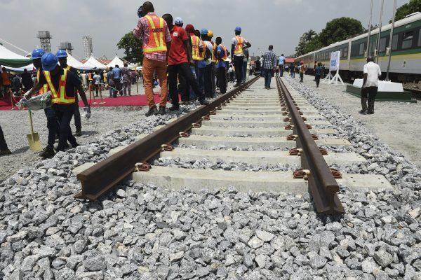 Des ouvriers nigérian le long d'un prototype de ligne de chemin de fer, qui sera construite par la China Railway Construction Corporation (CRCC), lors de la cérémonie de lancement du chantier de la ligne Lagos-Ibadan près du siège de la Nigerian Railway Corporation à Lagos, le 7 mars 2017. (Crédits : AFP PHOTO / PIUS UTOMI EKPEI)