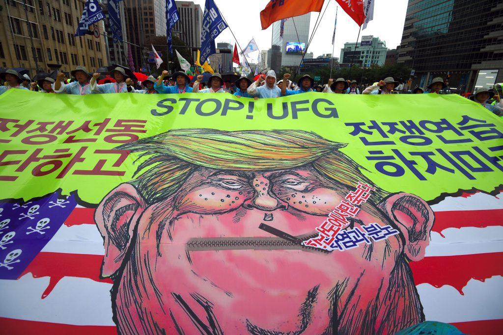 Des manifestants sud-coréens arborent une banderole avec une caricature du président américain Donald Trump lors d'une marche pour la paix dans la péninsule coréenne, près de l'ambassade américaine à Séoul le 15 août 2017. (Crédits : AFP PHOTO / JUNG Yeon-Je)